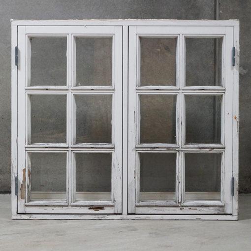 Ældre sidehængt vindue med sprosser og forsats ruder.