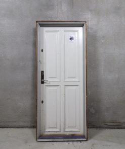 Flot opgangsdør i karm med 4 fyldninger på den ene side og glat på den anden. Døren er venstrehængt og kommer fra markant 5 etages hjørneejendom på strøget i København, Frederiksberggade 2 / Gammeltorv 24.