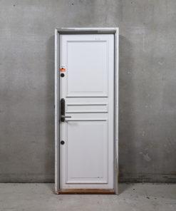 Venstrehængt opgangsdør i karm. Døren er med fyldning på den ene side, glat på den anden og udstyret med rustfri briklås.