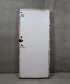 Opgangsdør i 120 mm karm. Døren er højrehængt, glat på den ene side hvor der er monteret metalplade på hele dørpladen, med indvendige træfyldninger og gammelt messing dørhåndtag samt nøglehul med klap.