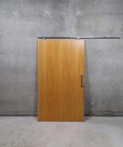 Skydedørsplade der måler 112,5 x 203,5 cm med skinne i 200 cm længde. Døren er brugt og stammer fra offentlig bygning.