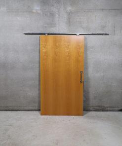 Skydedørsplade der måler 102,5 x 203,5 cm med skinne i 200 cm længde. Døren er brugt og stammer fra offentlig bygning.